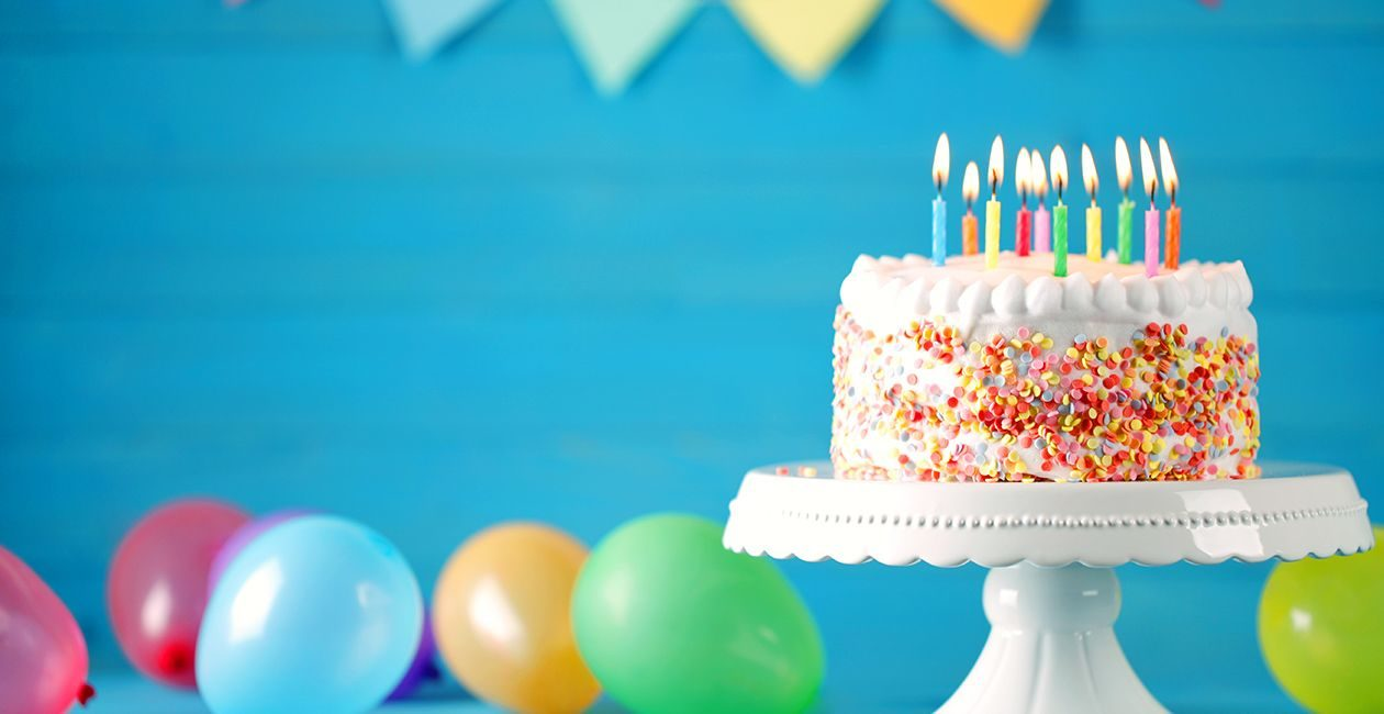 Photograph showing birthday cake and baloons